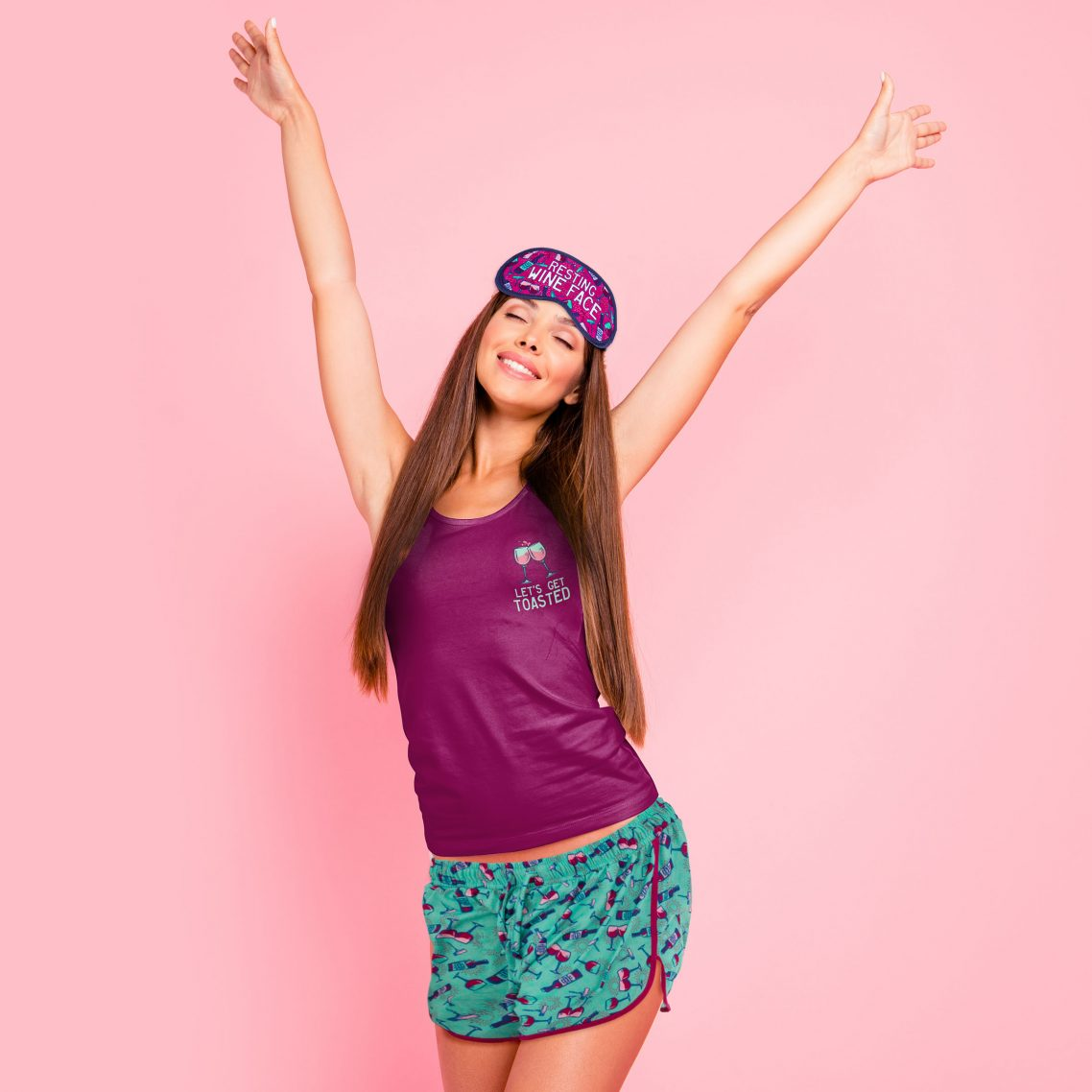 Young gorgeous smiling lady wearing eye mask and night wear, stretching. Isolated over pink pastel background